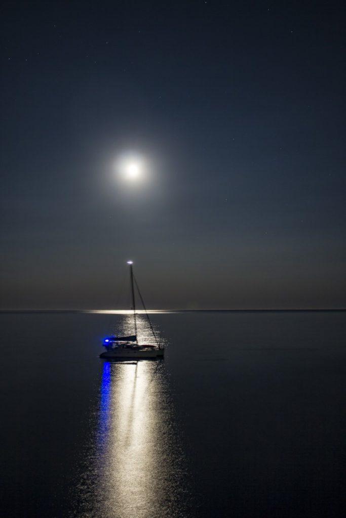 barca a vela e riflesso della luna